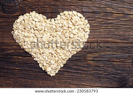 Heap of oat flakes in a shape of heart on dark wooden background - stock photo