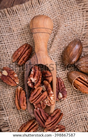 Heap of Pecan Nuts (selective focus) on an old wooden table - stock photo