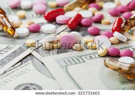 Heap of pharmaceutical drug and medicine pills scattered on dollar cash money, cost of medicinal product and treatment concept - stock photo