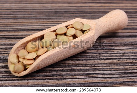 Heap of raw green lentil on wooden spoon lying on wooden background, concept for healthy nutrition and eating - stock photo