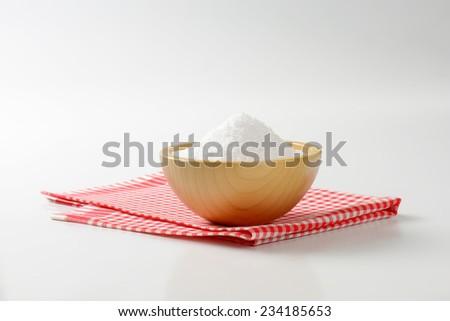 heap of salt in the wooden salt cellar on the fabric linen - stock photo