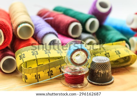 heap of sewing color bobbins threads, measure tape and old thimble on wooden table with blur background   - stock photo