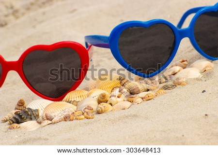 Heap of shells and colorful sunglasses in shape of heart lying on sand at the beach, summer time, symbol of love - stock photo