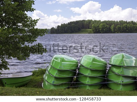 Heap of stacked boats on the lake shore - stock photo