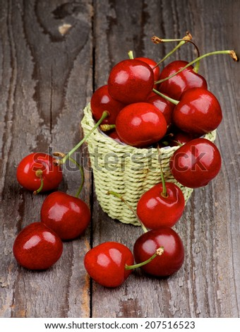Heap of Sweet Cherries in Green Wicker Basket isolated on Rustic Wooden background - stock photo