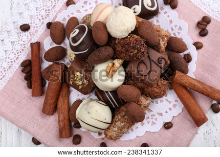 Heap of sweet chocolates with coffee beans on pink material and white doily on wooden background - stock photo
