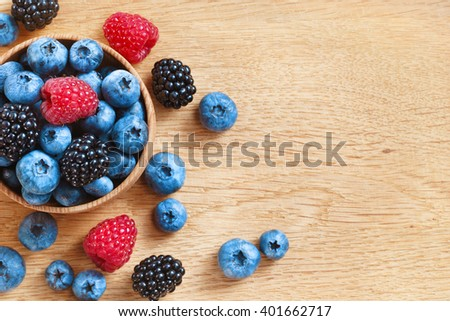 Heap of sweet tasty berries on wooden table. Close up, top view, high resolution product. Harvest Concept - stock photo
