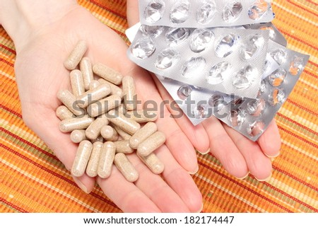 Heap of tablets and empty pills blisters lying in hand of woman - stock photo