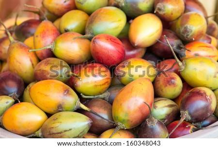 Heap of Tamarillo fruits on a open market - stock photo
