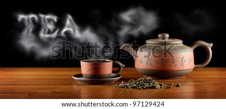 """heap of tea, kettle and cup with hot tea and word """"tea"""" - stock photo"""