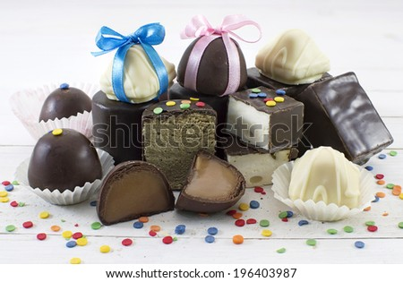Heap of the decorated chocolate candies in assortment on white - stock photo