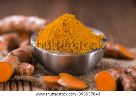 Heap of Turmeric (selective focus) on an old wooden table - stock photo