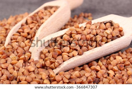 Heap of uncooked brown buckwheat groats with wooden spoon lying on structure of concrete, concept for healthy eating and nutrition - stock photo
