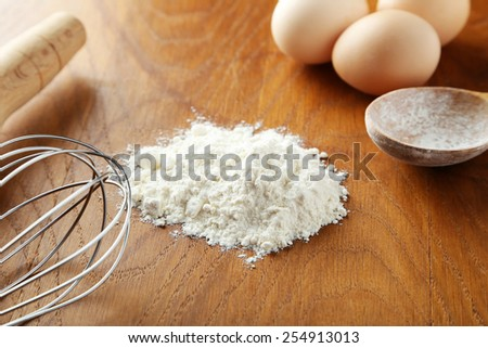 Heap of wheat flour with eggs and spikelets on brown wooden background - stock photo