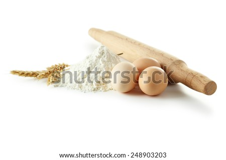 Heap of wheat flour with eggs, rolling pin and spikelets isolated on white - stock photo