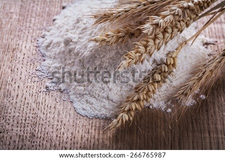 heap of white flour with ears of wheat and rye on wooden board  - stock photo