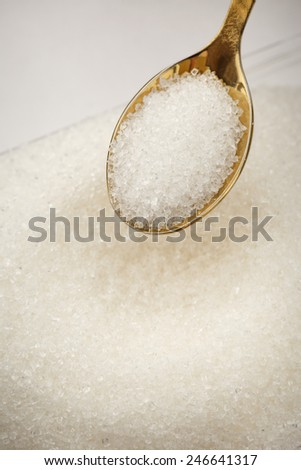 Heap of white sugar and golden spoon - stock photo