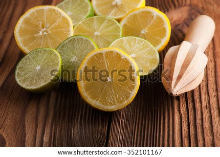 Heap of whole and sliced lemons and limes    and citrus reamer over wooden background. Top view - stock photo