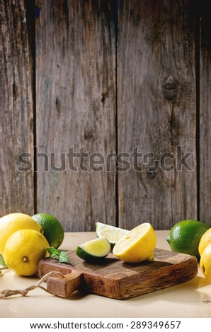 Heap of whole and sliced lemons and limes on little wooden cutting board over wooden background. Rustic sun light. - stock photo