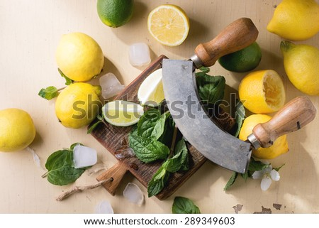 Heap of whole and sliced lemons, limes and mint with knife and ice cubes on little wooden cutting board over wooden background. Rustic sun light. Top view. - stock photo