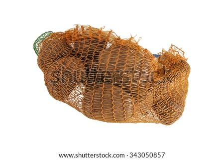 Heap of yellow raw potatos in red string bag - stock photo