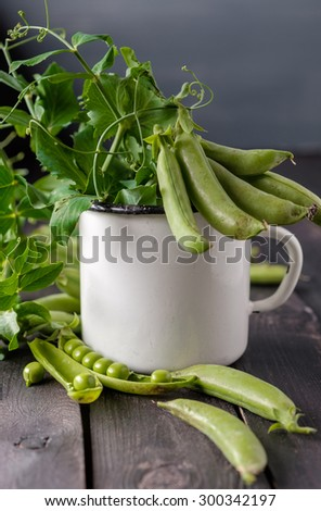Heap of young green peas whole and broken with leaves and flower in vintage cup over old wooden table. Dark rustic style.  - stock photo