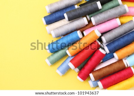 Heap spool of sewing threads on yellow background - stock photo