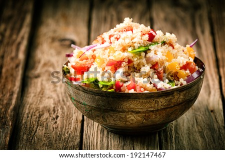 Heaped rustic bowl of savory quinoa with herbs, peppers and tomato for a healthy vegetarian dish rich in protein and nutrients standing on old wooden boards - stock photo