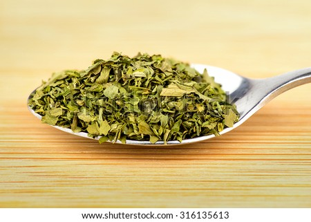 Heaped spoonful of dried parsley leaves - stock photo