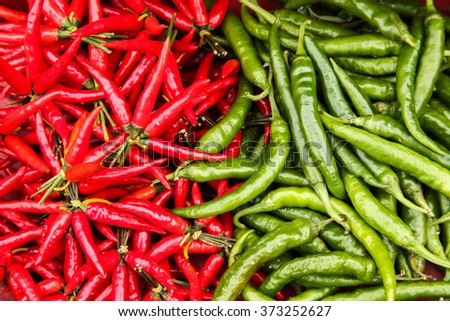 heaped up pile of green and red chillies - stock photo