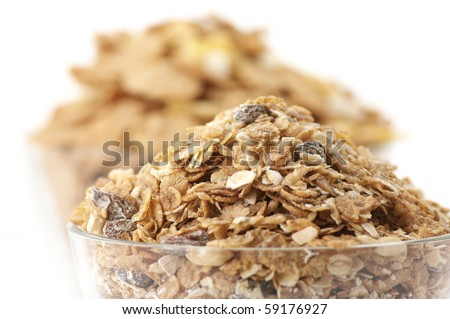 Heaps of breakfast cereals close-up in glass bowls on white background. - stock photo