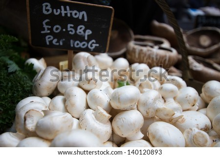 Heaps of button mushrooms for sale at farmers market. Shallow depth of field. - stock photo