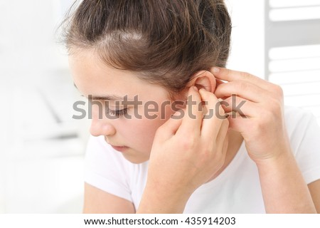 Hearing aid for your child . The girl assumes hearing aid. - stock photo