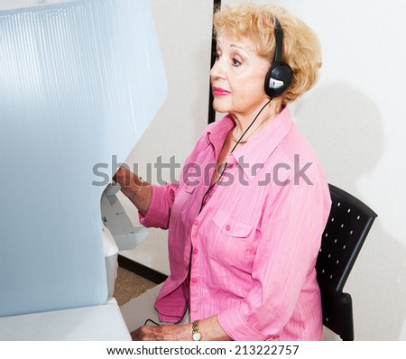 Hearing disabled senior woman voting on touch screen machine with headphones.   - stock photo
