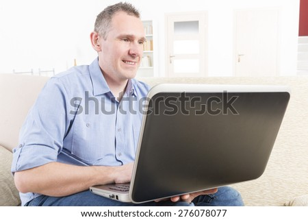 Hearing impaired man working with laptop at home or office - stock photo