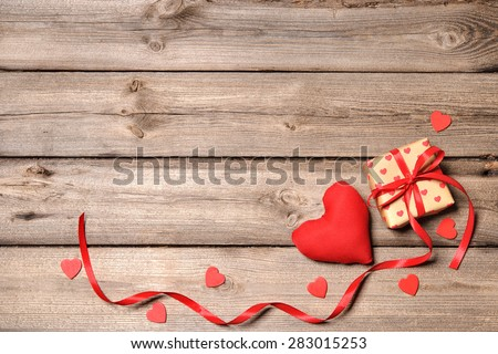 Heart and gift box with red ribbon on wooden background - stock photo