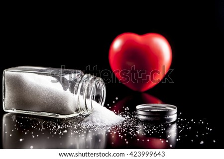 Heart and salt isolated on black background with reflection - stock photo