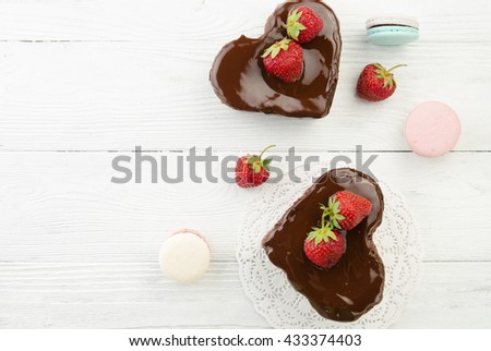 Heart cake and french macarons. Pieces of chocolate cake with fresh strawberry on wooden background. Top view. - stock photo