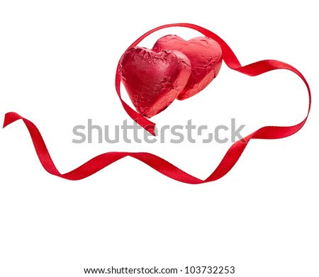 Heart candies in foil with red ribbon on white background - stock photo