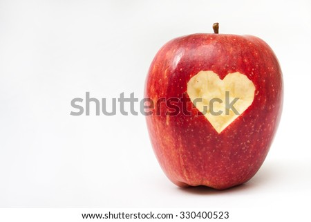 Heart carved into red apple. - stock photo