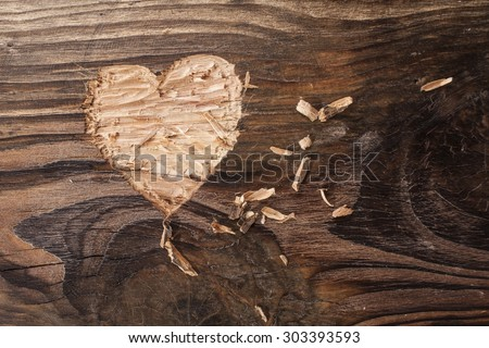 Heart carved into wooden plank - stock photo
