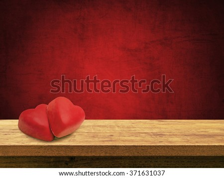 Heart chocolates on wooden table against red textured wall background, vintage effect - stock photo