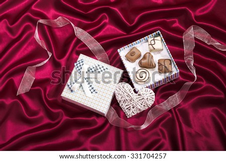 Heart  decoration with chocolate candys in gift box on red satin background - stock photo