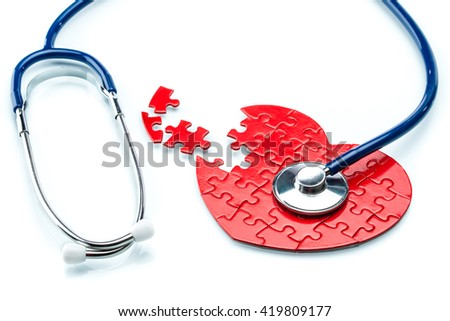 Heart disease, puzzle heart with stethoscope on white background - stock photo