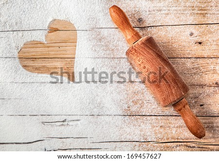 Heart drawn in scattered flour alongside an old wooden rolling pin depicting love of cooking or romance with copyspace for your greeting or message - stock photo