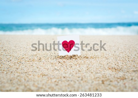 Heart drawn on a little piece of paper at the beach - stock photo