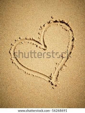 Heart drawn on sand. - stock photo