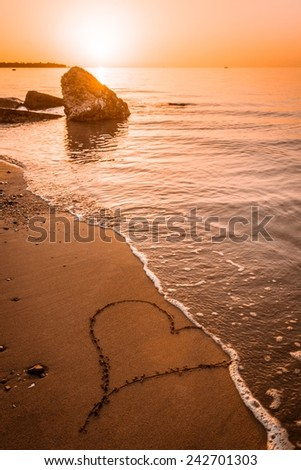 Heart drawn on the beach sand with sun above the horizon being washed away - stock photo