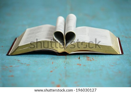 Heart formed by open Bible on vintage table - stock photo