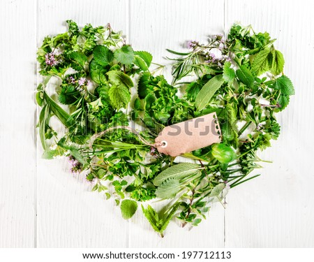 Heart formed of assorted fresh green culinary herbs including parsley, thyme, rosemary, basil and chives with a blank brown gift tag on rustic white painted boards symbolic of love and romance - stock photo